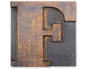 Antique wood cut block of the letter F